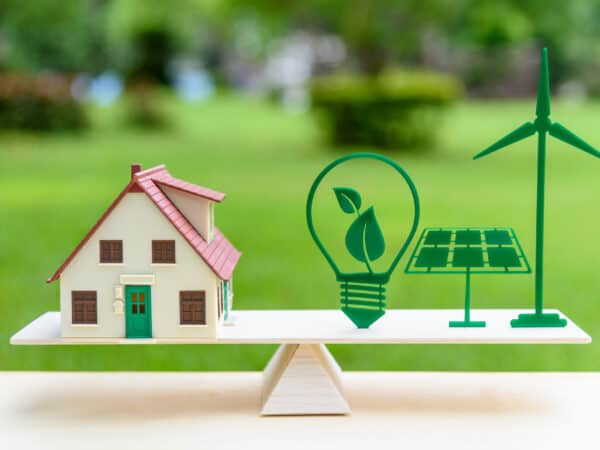 Future clean / renewable or alternative energy for modern living concept : House model, light bulb with green leaf, solar panel, wind mill on wood balance scale, depicts the awareness of environment.